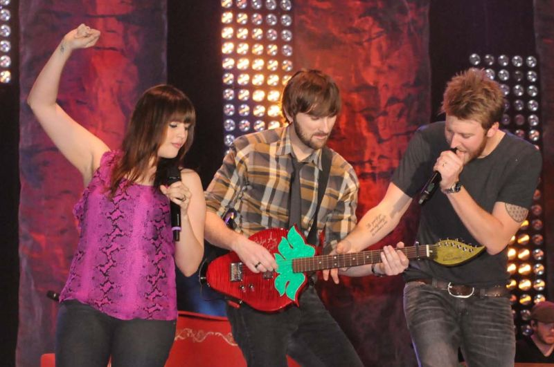 Lady Antebellum Paying a Musical Harvest Strawberry Guitar on stage at the Florida Strawberry Festival in support of Migrant Farm Workers Scholarship Charity